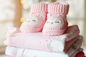A knitted pink baby shoes with cute owl design placed above some soft fabrics which is folded properly.