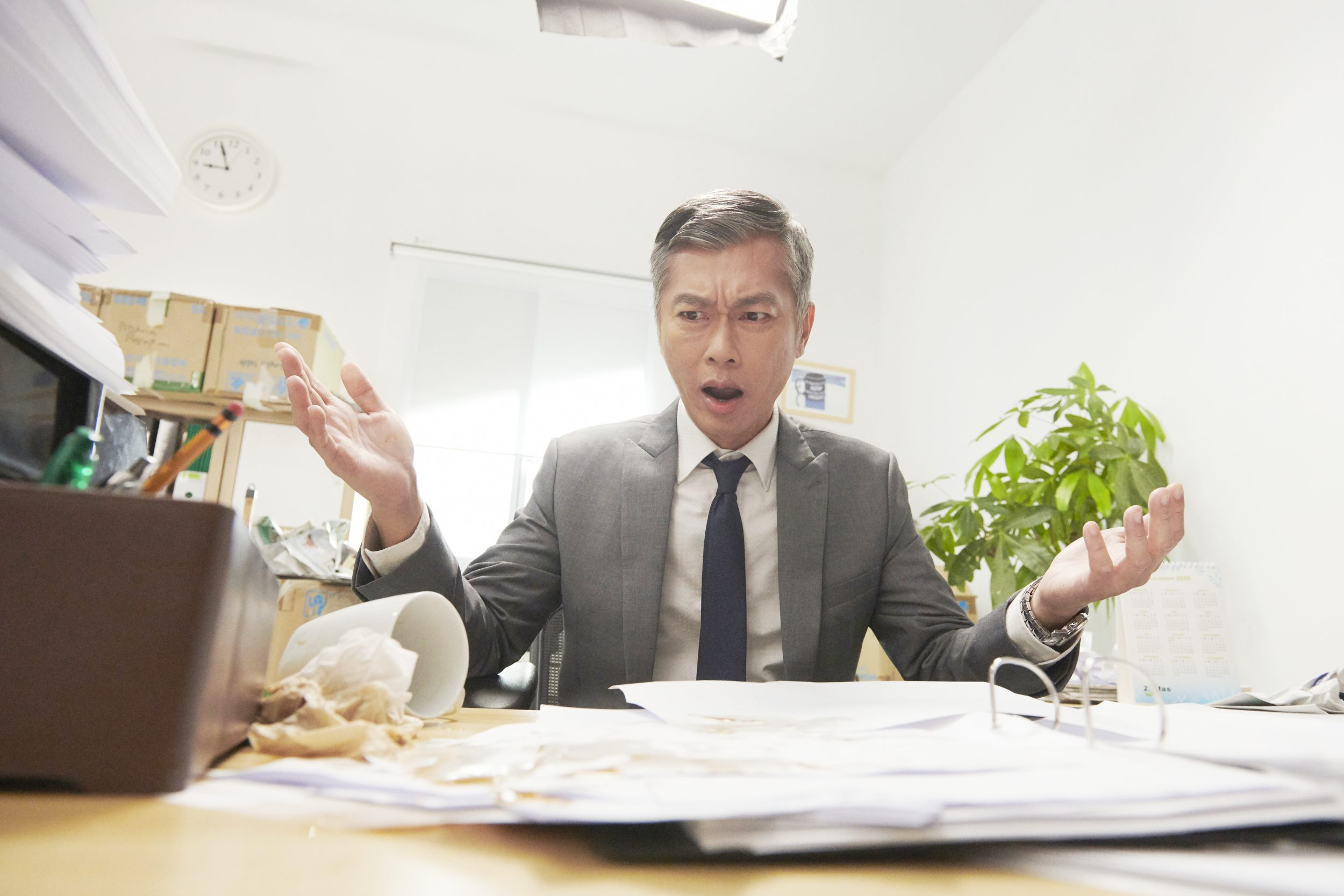 Mad office worker who is obviously irritated and complaining about spilling his food and having messy table