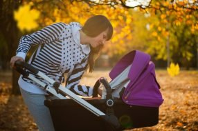 A mother checking on her baby in a stroller under maple trees during fall