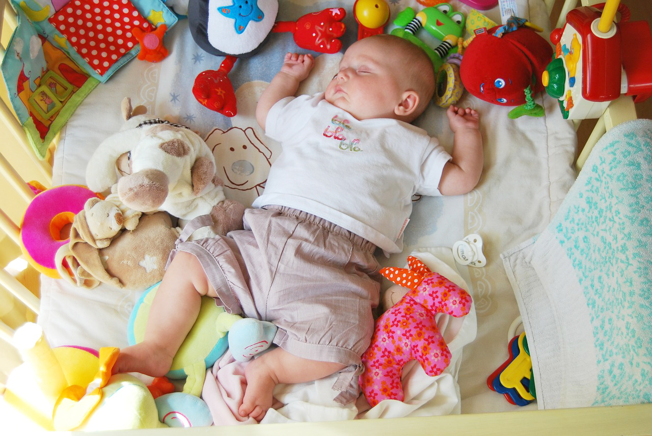 Cute baby boy sleeping inside a cradle with many plush toys surrounding him.