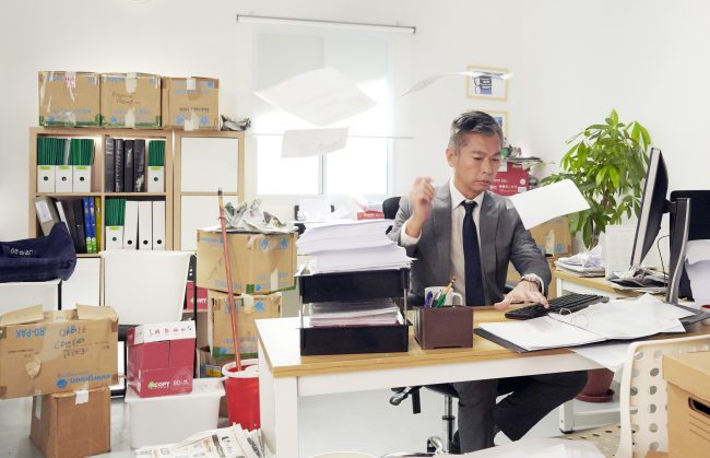 An office worker in a gray suit throwing paper works in a messy and cluttered office with many unorganized things and boxes